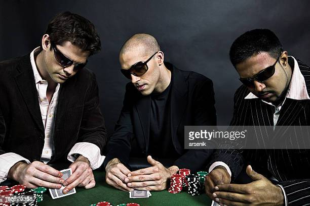 Three Men Sitting at Table Playing Poker and Checking Cards