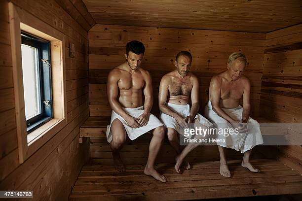 Three men sitting in sauna with heads bowed