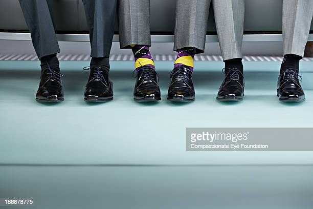 three men sitting on bench, view of shows - individuality stock pictures, royalty-free photos & images