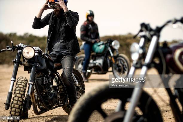 three men sitting on cafe racer motorcycles on a dusty dirt road. - motorcycle biker stock pictures, royalty-free photos & images