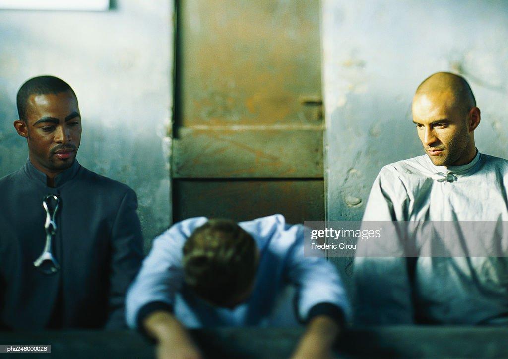 Three men sitting, one leaning forward : Stockfoto