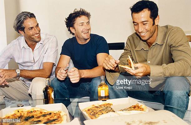 Three men sitting together and eating pizza