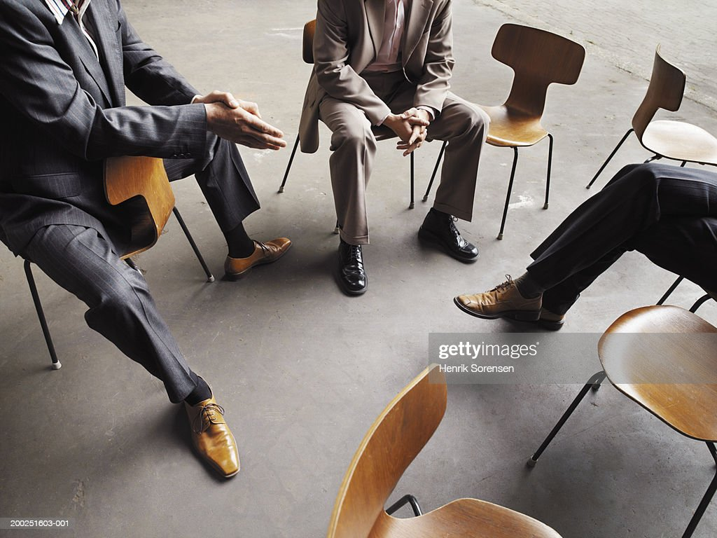 Three men sitting together by empty chairs : Foto de stock