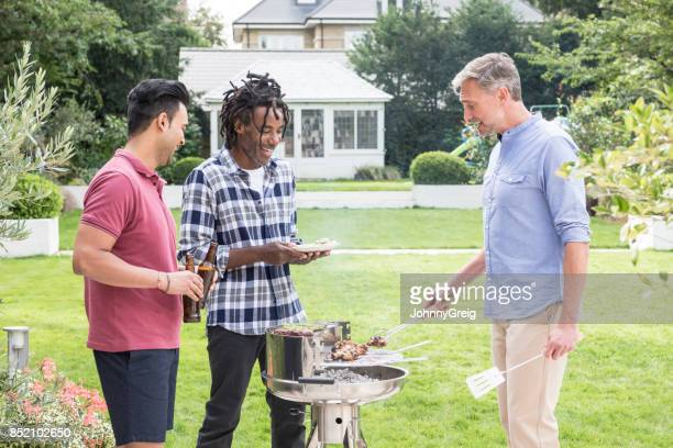 Three men smiling and enjoying barbecue in back garden