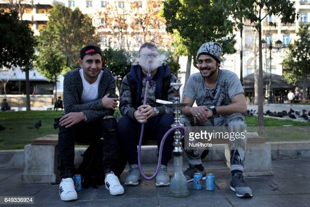 Three men smoking hookah in Syntagma square in Athens, Greece, March 7, 2017.