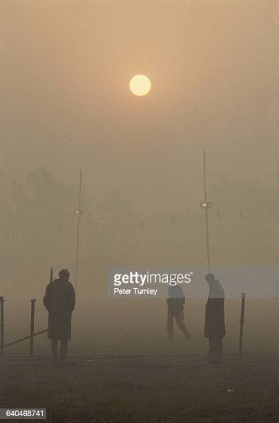 Three men stand in the fog of New Delhi the morning of Indira Gandhi's funeral 1984