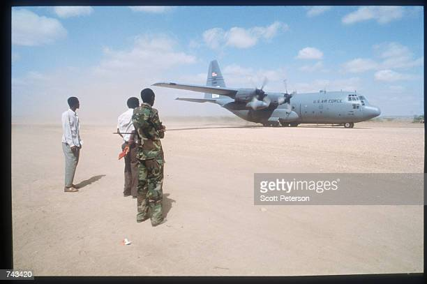 Three men stand on a runway while the US organized air bridge of food is flown to Somalia August 28 1992 from Mombasa Kenya In August the US...