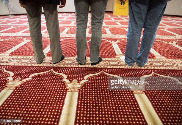 Three men stand on the carpet in the prayer room of the BaitulWahid mosuqe which is situated in a former Aldi branch in Hanau Germany 28 September...