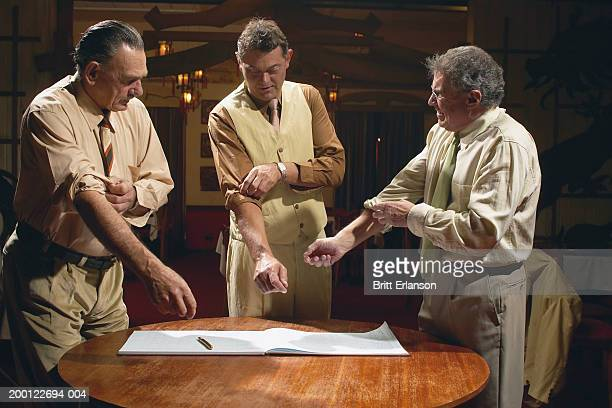 Three men standing behind book on table, rolling up sleeves