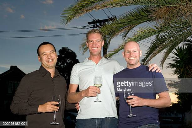 Three men standing in garden holding glasses of wine, smiling