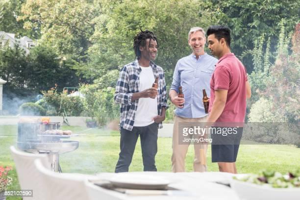 Three men standing in garden with bbq chatting
