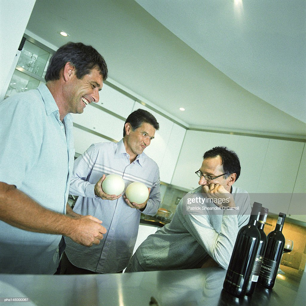 Three men standing in kitchen, one holding melons : Stockfoto