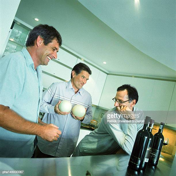 Three men standing in kitchen, one holding melons
