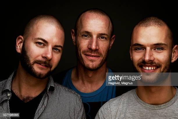Three men standing, smiling, portrait