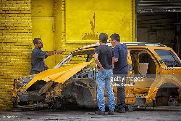 CONTENT] three men survey damage possible salvage of taxi cab in bad condition on street in Astoria Queens New York City