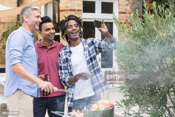 Three men taking selfie with phone by barbecue