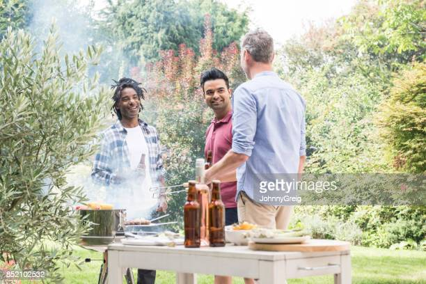 Three men talking in garden with barbecue