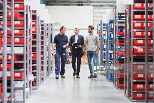 three men talking in storehouse of a factory - maglietta polo foto e immagini stock