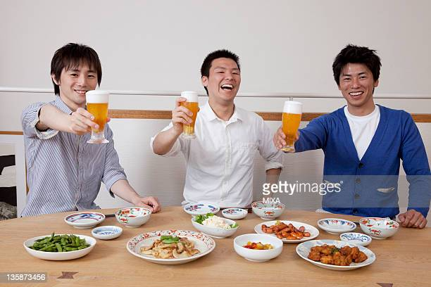 Three men toasting at home party