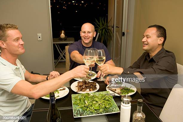 Three men toasting glasses at dinner, smiling