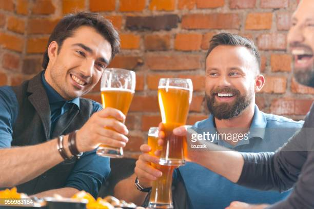 three men toasting with beer glasses in the pub - izusek stock pictures, royalty-free photos & images