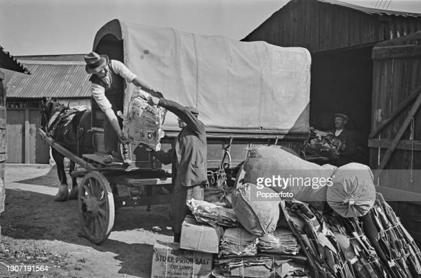 Three men unload bales of newspaper and cardboard from a horse drawn cart for recycling at farm buildings in the village of Holsworthy, Devon,...