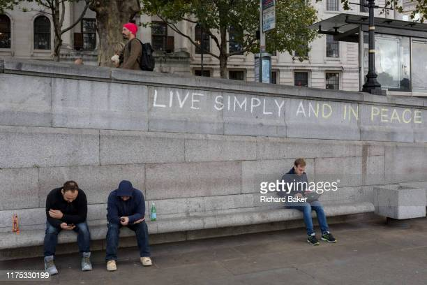 Three men use their phones and a laptop beneath the slogan 'Live Simply and Live in Peace' has been written on a wall by an environmental activist...