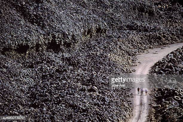 Three men walk through mountain of tires, California, USA.