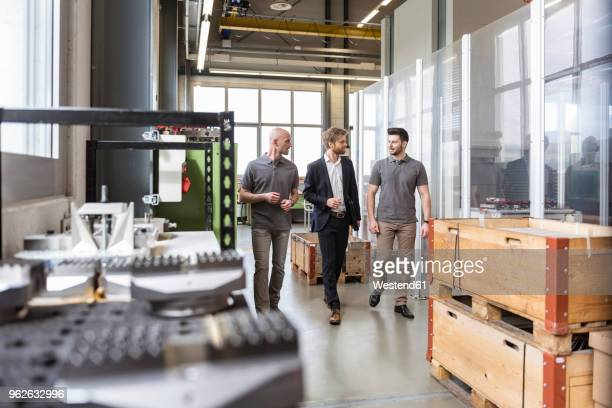 three men walking and talking in factory - finanzen und wirtschaft stock-fotos und bilder