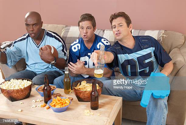 Three men watching football in living room