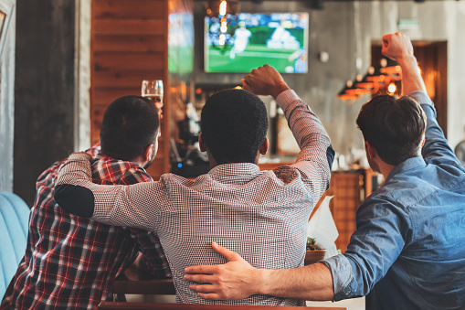 Three men watching football on TV in bar 1135937542