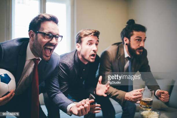 three men watching soccer game from home - mens world championship stock photos and pictures