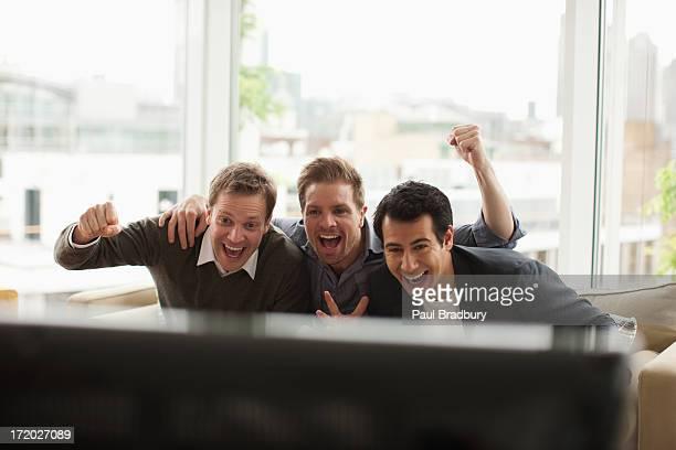 trois hommes regardant la télévision - seulement des adultes photos et images de collection
