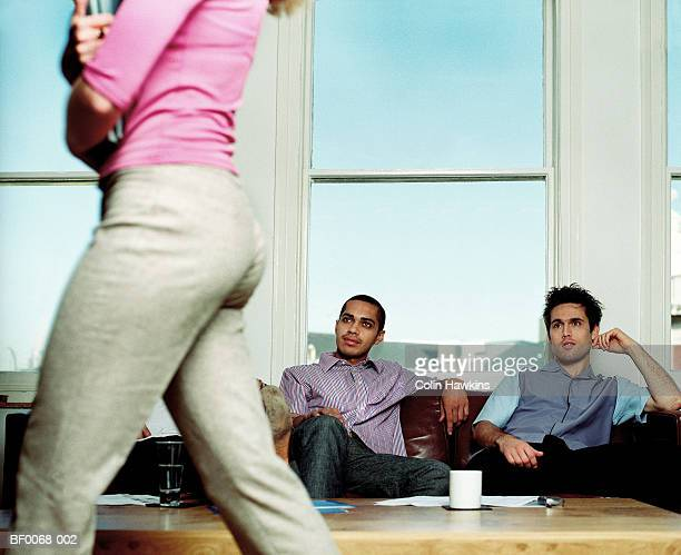 Three men watching woman walk past