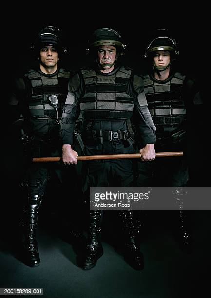 three men wearing body armor, man in center holding baton, portrait - riot police stock pictures, royalty-free photos & images
