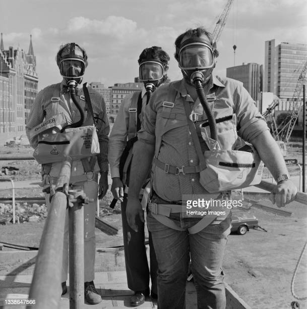 Three men wearing Draeger gas masks during a safety course at the British Library construction site. The British Library was designed by the...