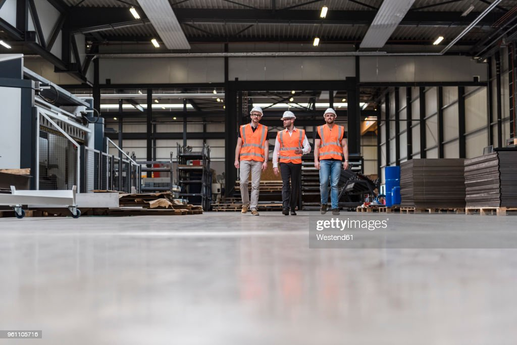 Three men wearing hard hats and safety vests walking on factory shop floor : ストックフォト