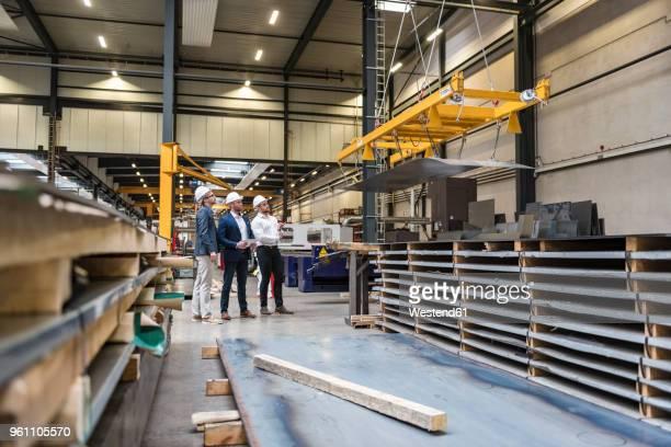three men wearing hard hats standing on factory shop floor - metallic suit stock photos and pictures