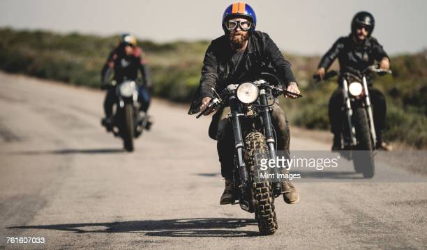 Three men wearing open face crash helmets and goggles riding cafe racer motorcycles along rural road.