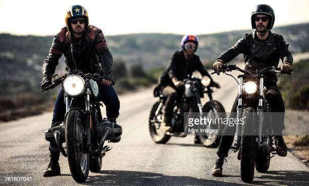 Three men wearing open face crash helmets and goggles sitting on cafe racer motorcycles on a rural road.