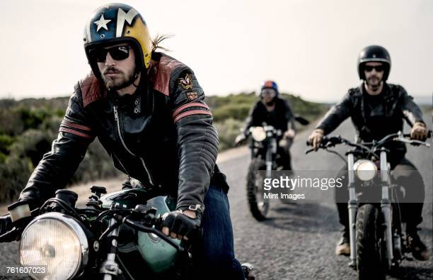 three men wearing open face crash helmets and sunglasses riding cafe racer motorcycles along rural road. - motorcycle biker stock pictures, royalty-free photos & images