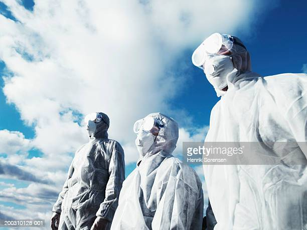 three men wearing protective suits, low angle view - protective suit stock pictures, royalty-free photos & images