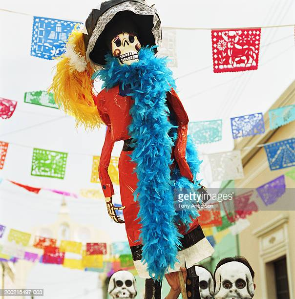 Three men wearing skeleton masks, holding up Day of the Dead puppet