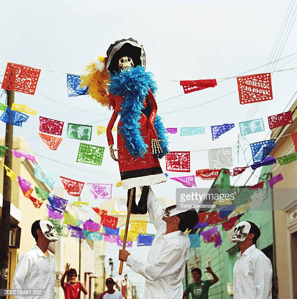 Three men wearing skeleton masks looking up at Day of the Dead puppet