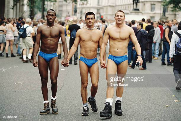 Three men wearing small blue swimming trunks taking part in the London Pride march, 1st July 2000.