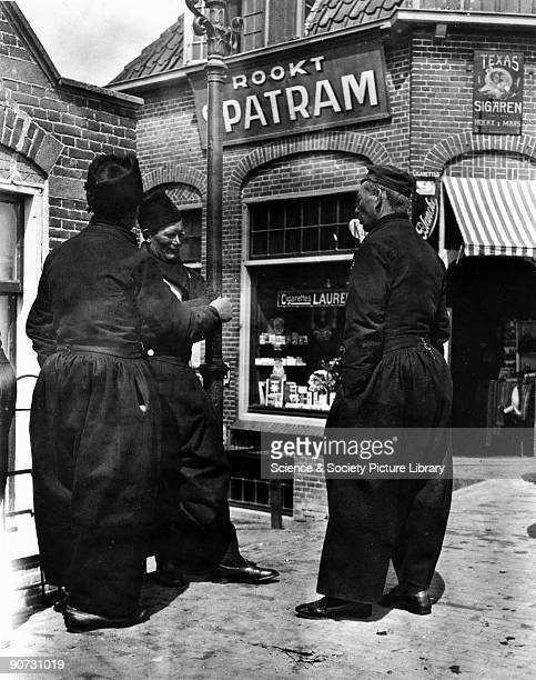 Three men wearing traditional Dutch costumes standing on a street corner in Holland c 1910s
