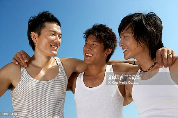 Three men with arms around one another