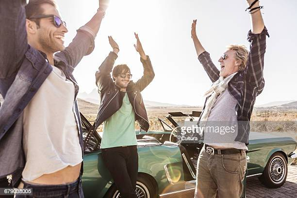 Three men with arms raised on roadside by convertible, Franschhoek, South Africa