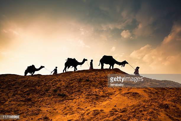 Three Men with Camels walking through Desert