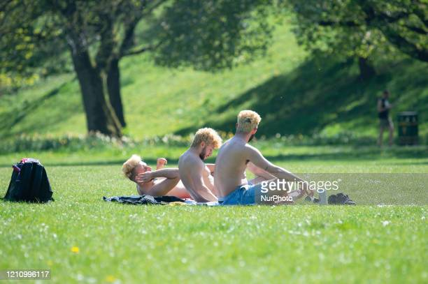 Three men with identical bleach blonde hair sunbathe in the sunshine in Peel Park Salford Greater Manchester on Saturday 25th April 2020
